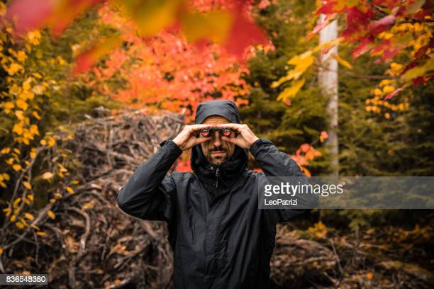 Man looking through binoculars in the forest