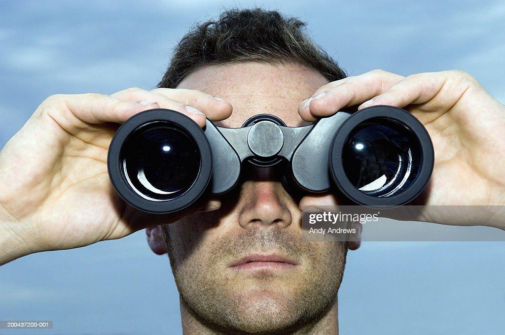 Man looking through binoculars outdoors, close-up : Stock Photo