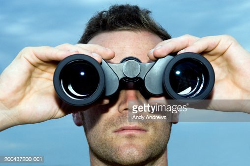 Man looking through binoculars outdoors, close-up : Stock Photo