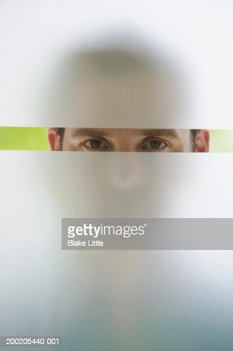Man looking through frosted glass window, portrait (upper section) : Stock Photo