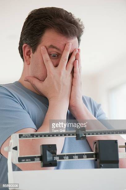 Man looking through hands at number on scale