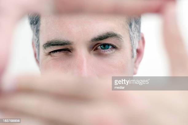 Man looking through hands in a rectangular shape