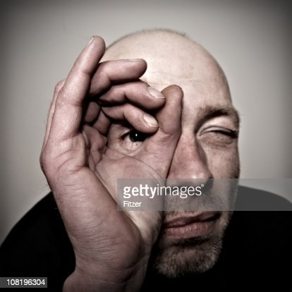 Man Looking Through Hole Made with Fingers : Stock Photo