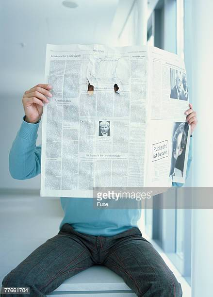 Man Looking Through Holes Ripped in Newspaper