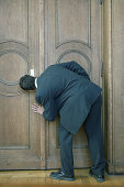 Man looking through keyhole of door, rear view