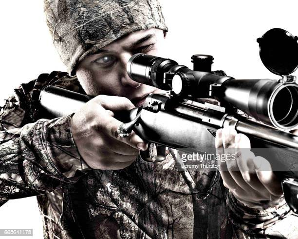 Man looking through scope in rifle wearing camouflage