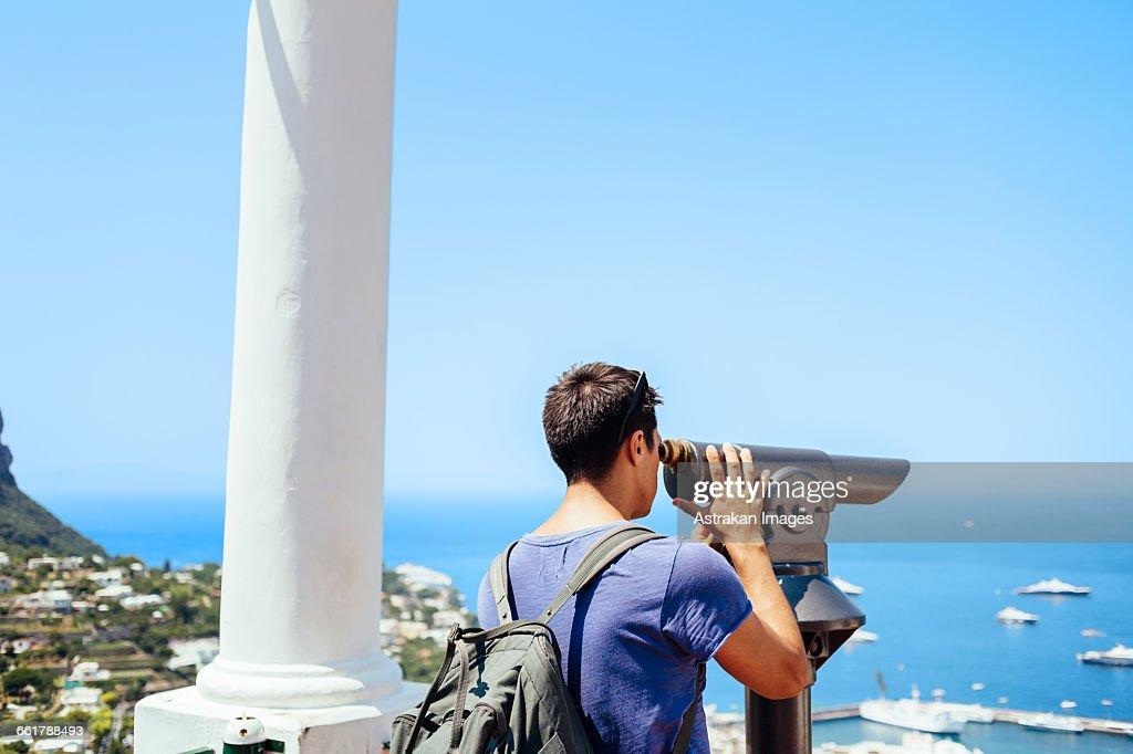Man looking through telescope at Amalfi Coast against sky