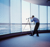 Man looking through telescope through office window