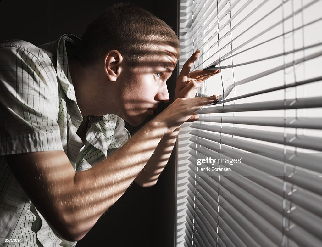 Man looking through the blinds. : Stock Photo