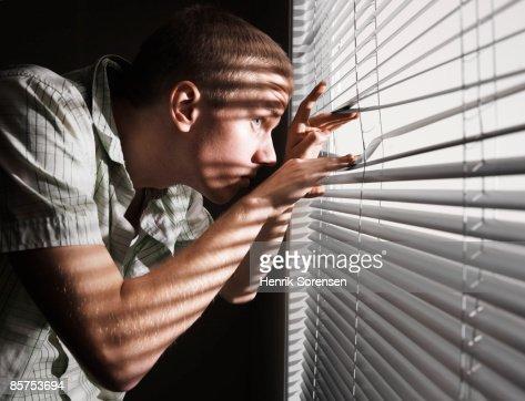 Man looking through the blinds.
