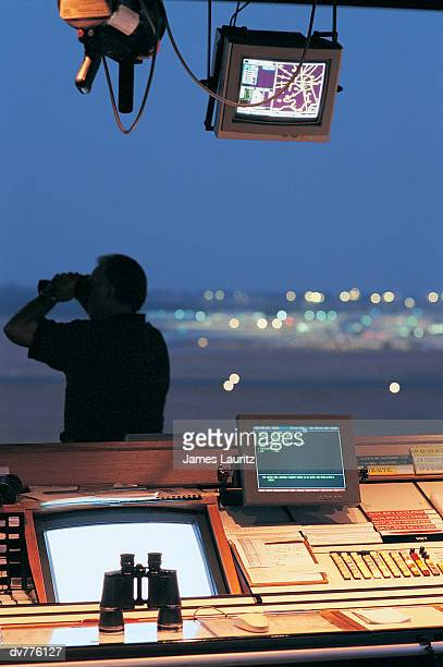Man Looking Through Window in Airport's Air Traffic Control