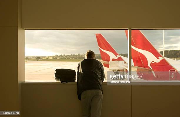 Man looking through window of Tullamarine Airport.