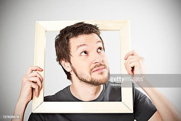 Uomo di guardare attraverso telaio in legno