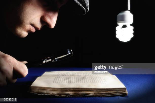 Man looking to an old book through magnifying glass
