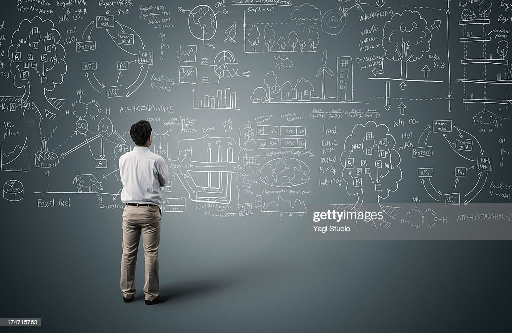 Man looking to formula and picture on blackboard : Stock-Foto