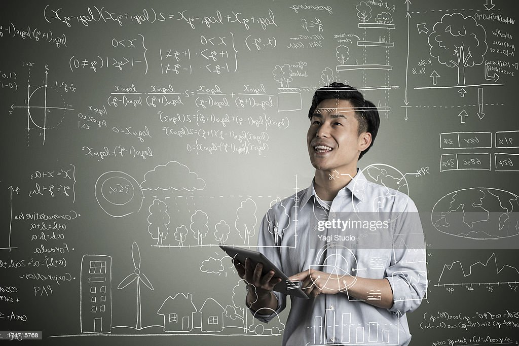 Man looking to formula and picture on blackboard