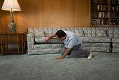 Man looking under sofa cushion