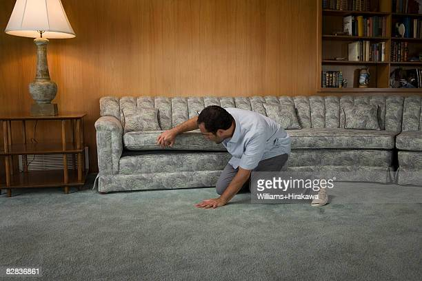 Man looking under sofa cushion