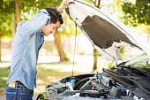 Portrait of stressed young man looking under the hood of his broken car
