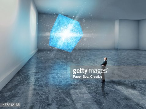 man looking up at a glowing blue 3D cube : Stock Photo