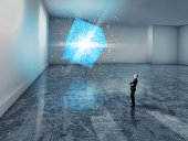 man looking up at a glowing blue 3D cube