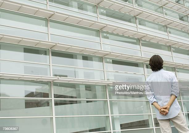 Man looking up at facade of office building