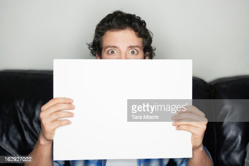 man looking wide-eyed holding blank sign