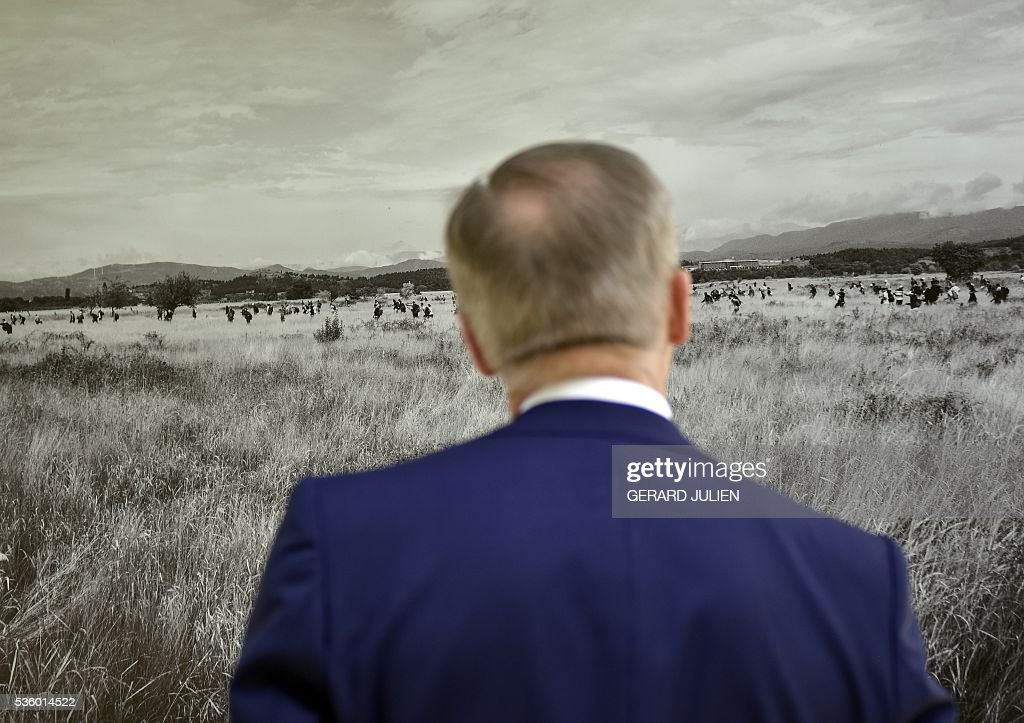A man looks a photog by French photographer Pierre Marsaut during the opening of the exhibition 'Caminos de Exilio' ('Ways of Exile') at Retiro Park in Madrid, on 31 May 2016. The exhibition shows pictures of refugees taken by five photographers; Sima Diab (Syria), Giorgios Moutafis (Greece), Manu Brabo (Spain), Olivier Jobard (France) and Pierre Marsaut (France) and has been organized by the French Embassy and the French Institute in Spain, on the sidelines photo festival of PhotoEspana 2016. / AFP / GERARD