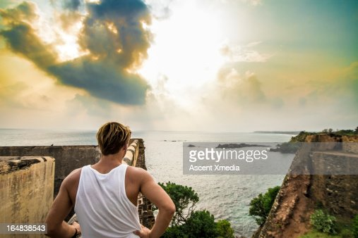 Man looks across fortress ruins to sea
