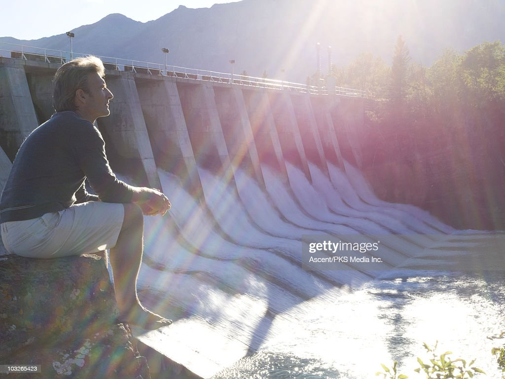 Man looks across hydroelectric dam, from rock seat