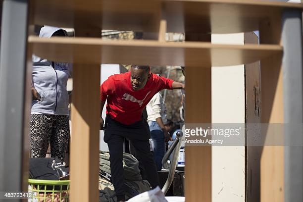 A man looks after his possessions as members of the socalled 'Red Ants' private security company hurl household items belonging to residents of the...