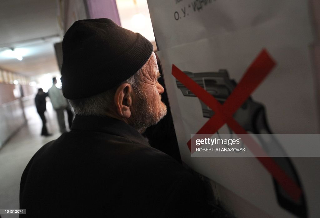 A man looks at a banner informing voters of the interdiction to carry firearms as he arrives to cast his ballot at a polling station in Skopje on March 24, 2013, as part of the local elections held against a backdrop of ethnic tensions, as a political crisis between the right-wing government majority and left-wing opposition rumbles on.