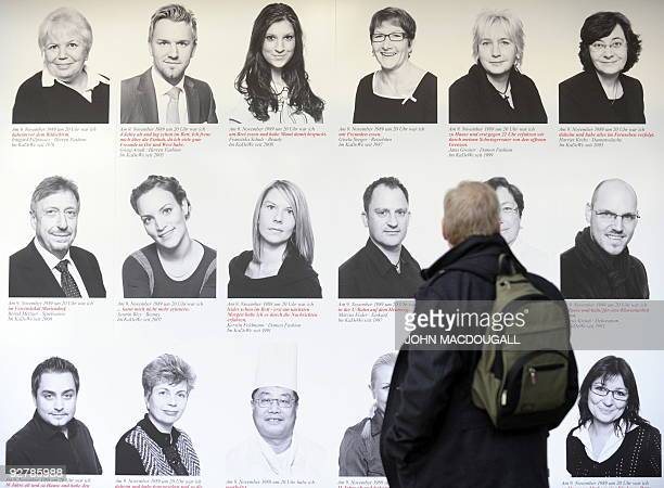 A man looks at a billboard featuring portraits of people and their recollections of the fall of the Berlin wall in 1989 at Berlin's KaDeWe department...