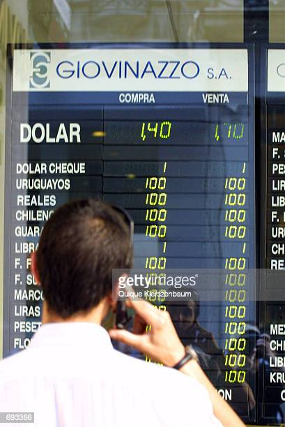 A man looks at a board reflecting currency exchange rates January 12 2002 in Buenos Aires Argentina Currency Exchange offices were reopened yesterday...