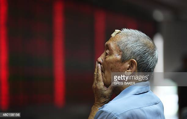 A man looks at a board showing stock market movements at a securities company in Beijing on July 10 2015 Chinese stocks surged for a second day on...