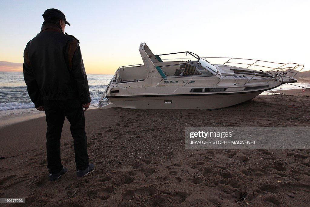 A man looks at a boat on January 5, 2014 which washed ashore on a beach in Cannes, southeastern France, after the area was hit by gale-force winds and pounding rain. AFP PHOTO / JEAN CHRISTOPHE MAGNENET