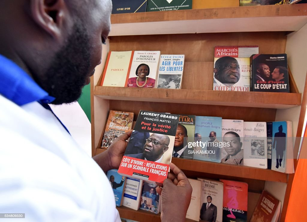 A man looks at a book about Former Ivorian president Laurent Gbagbo displayed during the International Book Fair of Abidjan on May 28, 2016. / AFP / SIA