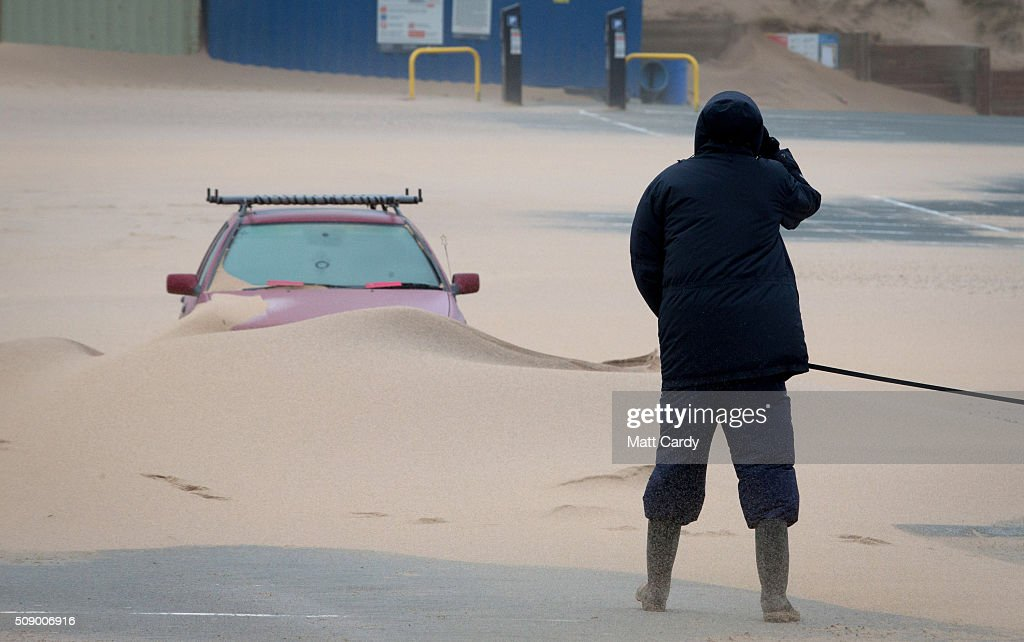 A man looks at a car that has been partially covered in sand in Fistral Beach car park on February 8, 2016 in Newquay, England. Parts of the UK are currently being battered by Storm Imogen, the ninth named storm to hit the UK this season. Thousands of homes have been left without power and commuters hit by road and rail chaos as Storm Imogen batters the South with gale force winds and torrential rain.
