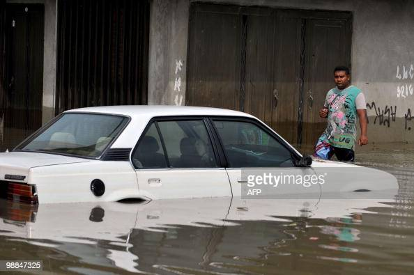 A man looks at a car that remains stranded in a flooded street in a neighborhood of Cali Valle del Cauca departament Colombia on May 4 2010 after the...