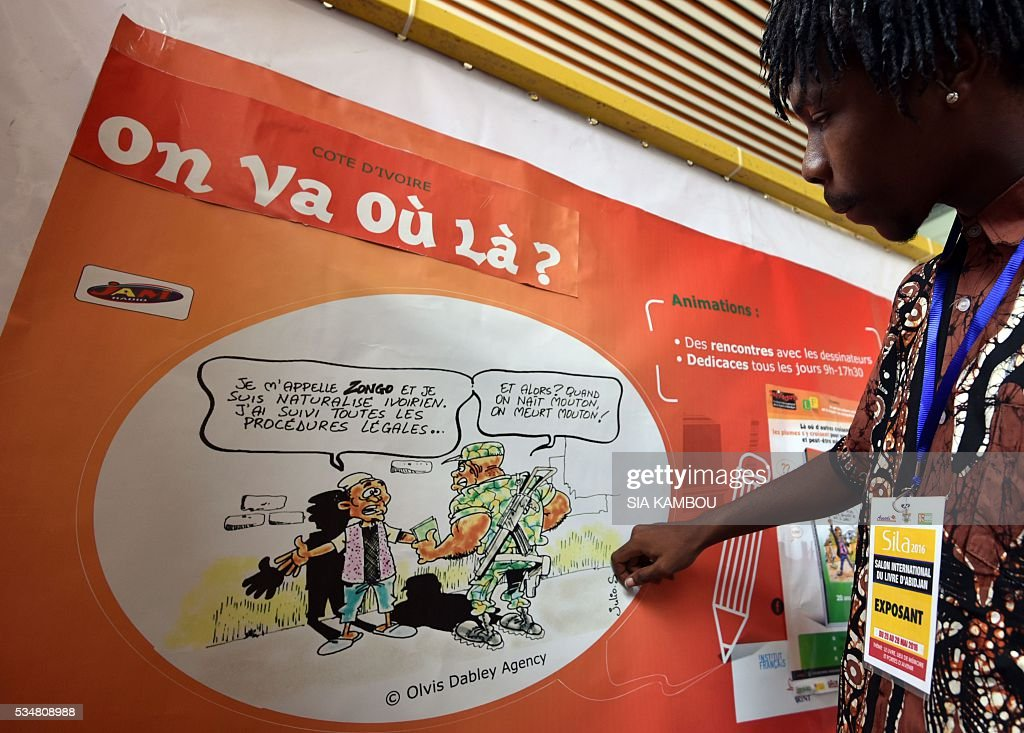 A man looks at a cartoon on Ivorian identity displayed during the International Book Fair of Abidjan on May 28, 2016. / AFP / Sia KAMBOU