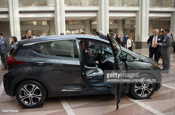 A man looks at a Chevrolet Bolt before attending a winter luncheon with Mary T Barra Chairman and CEO of General Motors Company in Washington DC on...