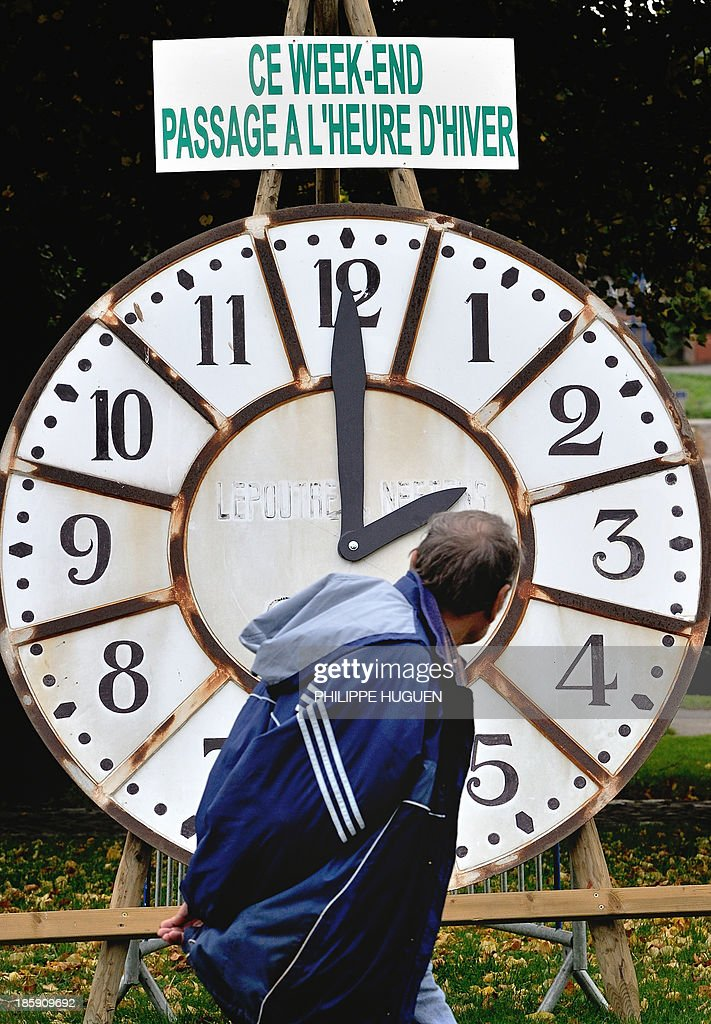A man looks at a clock with a sign reading 'This week-end switch to the winter time' in Godewaersvelde on October 26, 2013 ahead of the daylight saving time clock change ealry tomorrow.