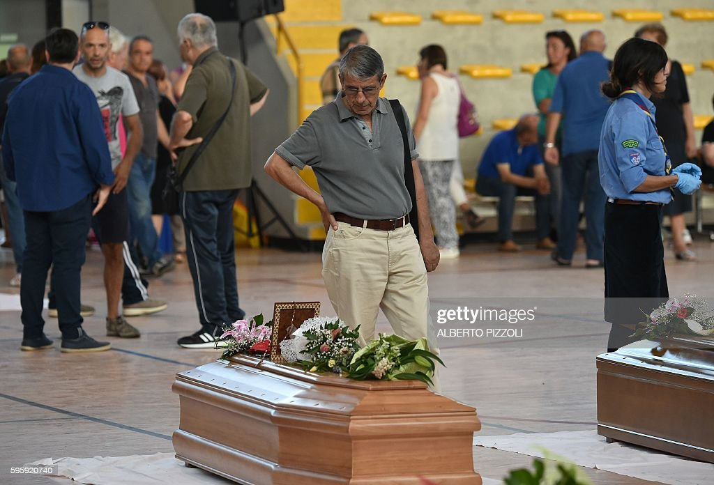 A man looks at a coffin of an earthquake victim in a gymnasium arranged in a chapel of rest on August 26 in Ascoli Piceno two day after a 62magnitude...