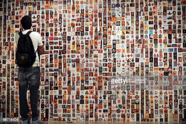 A man looks at a collage from the art exhibition 'Sagrado Corazon' by Colombian artist Carlos Carrillo during the XIV International Art Festival in...