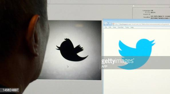 A man looks at a computer monitor showing the and old and new Twitter logos June 6 2012 in Washington DC Twitter unveiled the new 'Twitterbird' on...