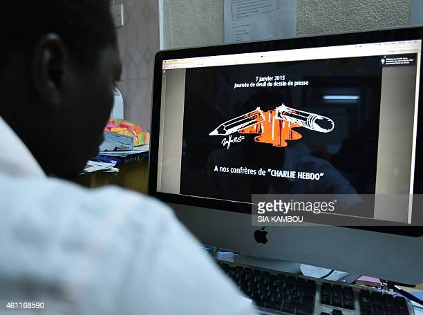 A man looks at a computer screen bearing a banner which translates as 'January 7 day of mourning for press cartoonists to our colleagues at Charlie...