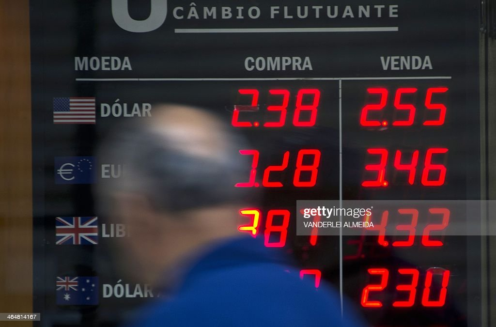 A man looks at a currency exchange bureau board announcing a rise of the US Dollar in relation with the Brazilian Real in the financial district of...