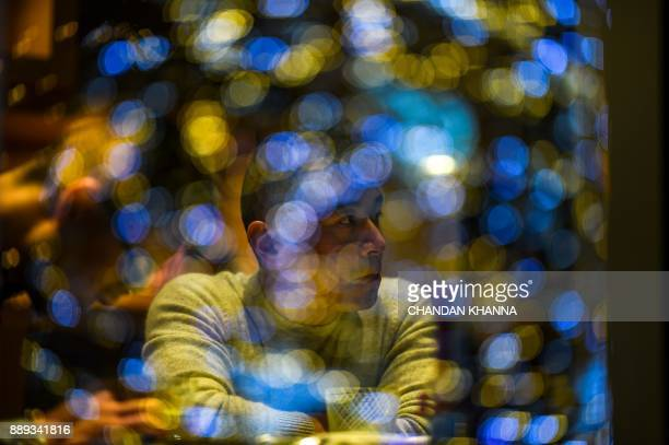A man looks at a decorated Christmas tree as he sits inside a cafe in Shanghai on December 10 2017 / AFP PHOTO / CHANDAN KHANNA