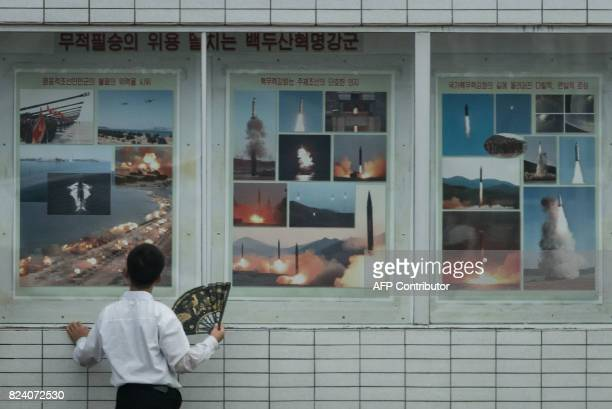 TOPSHOT A man looks at a display showing images of missiles launches and military exercises in a public square in Pyongyang on July 29 2017 / AFP...