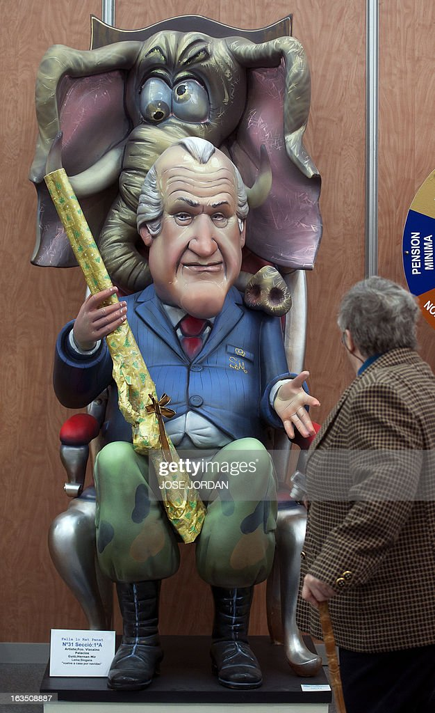 A man looks at a Falla, a gigantic sculpted structure of cardboard and wood which humorously portrays relevant current events and personalities, caricaturing Spain's King Juan Carlos, during an exhibition before preparations for the Fallas Festival, in Valencia on March 11, 2013. The Fallas will be burned in the streets of Valencia on March 19, 2013, as a tribute to St. Joseph, patron saint of the carpenters' guild.